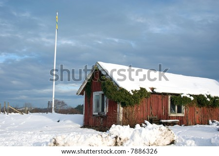 traditional swedish red cottage in snow - stock photo