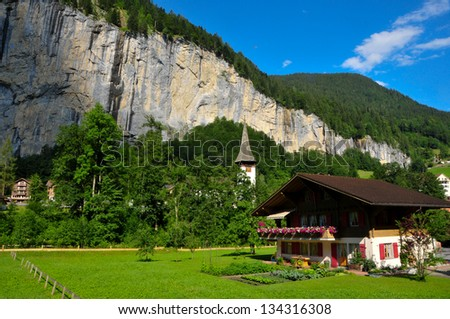 Traditional swiss chalet and church bell