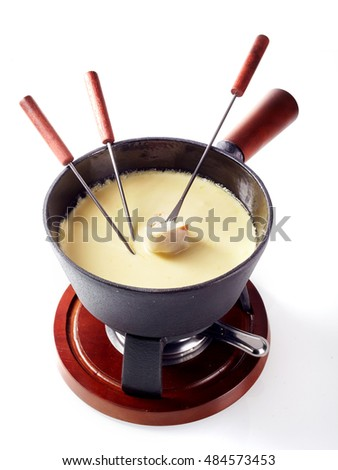 Traditional Swiss cheese and wine fondue in a pot with burner and long handled forks with bread for dipping isolated on white, high angle view