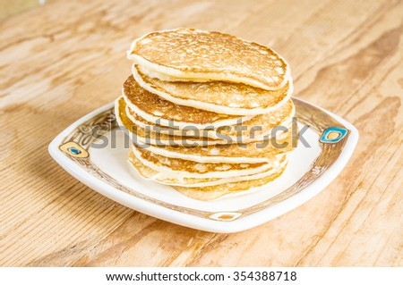 Traditional tasty delicious pancakes in decorative ceramic plate on wooden table. - stock photo
