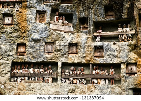 Traditional Tau tau, wooden statues representing dead men in a rock wall near Lemo, Sulawesi, Indonesia - stock photo