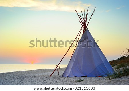 Traditional Teepee on a sea beach at beautiful sunset - stock photo