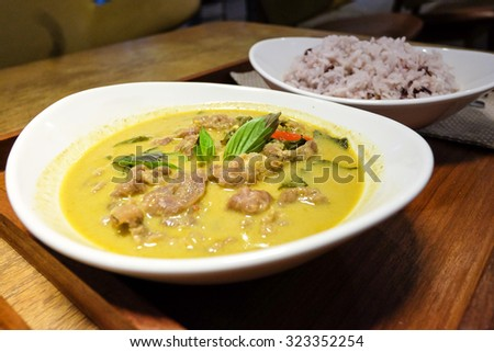Traditional Thai Beef green curry and boiled brown rice on the wood plate