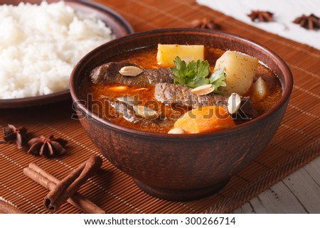 Traditional Thai beef massaman curry with peanuts close-up in a bowl. Horizontal - stock photo