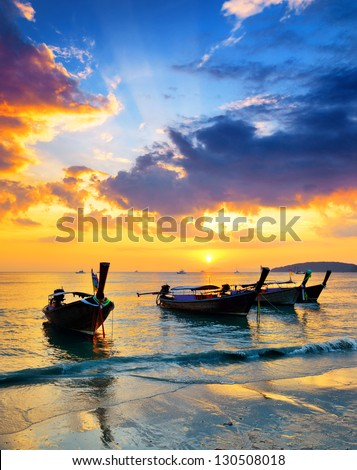 Traditional thai boats at sunset beach. Ao Nang, Krabi province. - stock photo