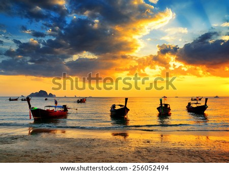 Traditional thai boats at sunset beach. Ao Nang, Krabi province. - stock photo