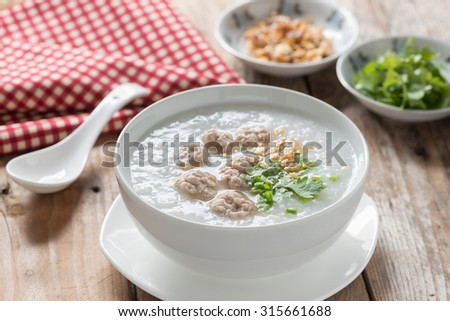 Traditional thai congee with minced pork in white bowl.