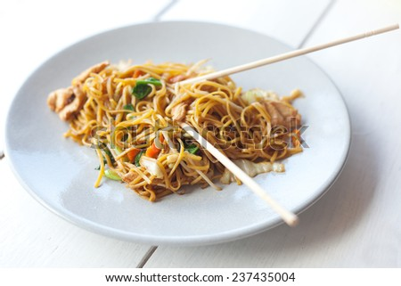 traditional Thai food, pad thai, noodles with vegetables and meat on the table - stock photo