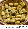 Traditional Thai food style, Glutinous rice steamed in banana leaf ( Khao Tom Mat or Khao Tom Pad ) bananas and sticky rice inside on wicker basket in culture market at Thailand - stock photo
