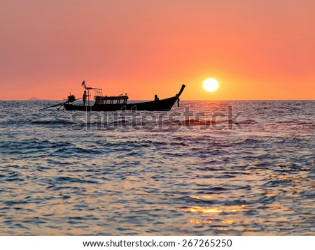 Traditional thai longtail boat against sunset above ocean, Thailand, Krabi province, Andaman sea - stock photo