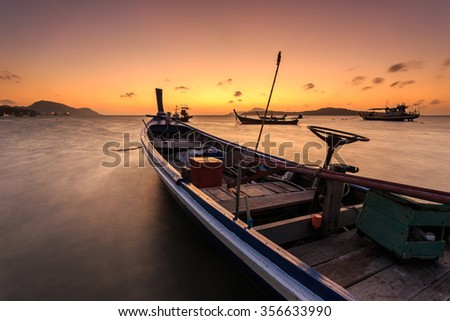 Traditional Thai longtail boat at sunrise beach in Phuket, Thailand