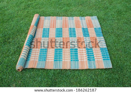 Traditional Thai mat on the green grass, a half of expand