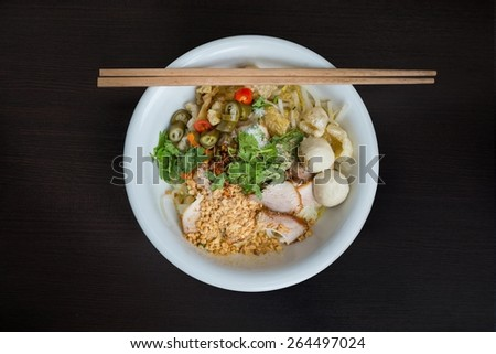 Traditional Thai noodle with meat ball and roasted red pork topped with pickled chilli, red pepper, sugar and crispy pork skin - stock photo