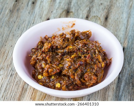 traditional Thai style raw preserved fish(thai accent is Pla-ra) with prepare herb and spice ingredient in plate on wood table - stock photo