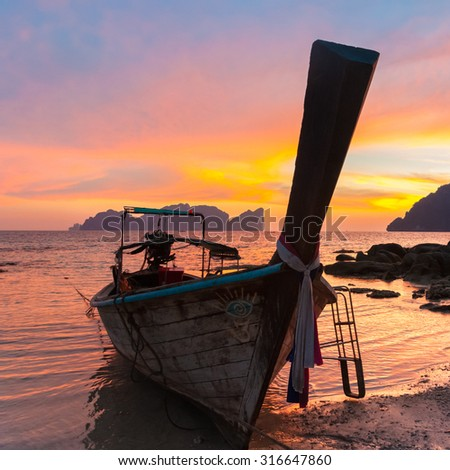 Traditional thai wooden longtail boat on beach of Phi-Phi Don island in sunset. Silhouette of famous Phi Phi Lee island in background. Thailand, Krabi province. - stock photo