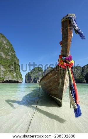 Traditional Thai wooden longtail boat with decorative sash ribbons at Maya Bay on Koh Phi Phi Leh - stock photo