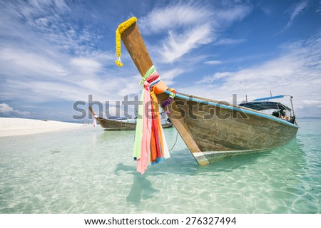Traditional Thai wooden longtail boat with decorative sash ribbons moored in crystal waters on the shore of Bamboo Island near Krabi - stock photo