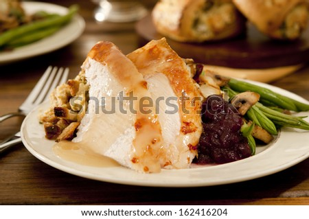 Traditional thanksgiving turkey dinner with cranberry sauce, stuffing, green beans, mushrooms and mashed potatoes. - stock photo