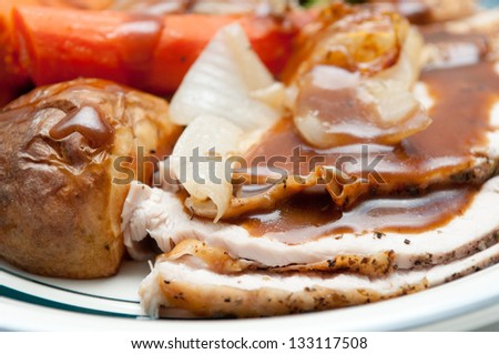 traditional Thanksgiving turkey dinner with crispy skin, turkey slices and fresh roasted  vegetables smothered in gravy - stock photo