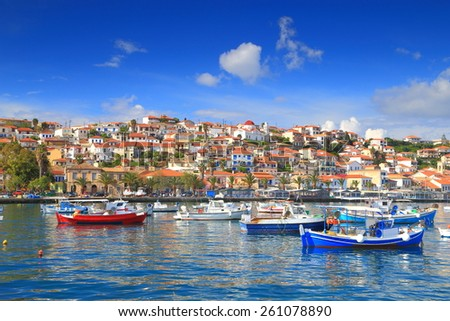 Traditional town on a hillside and fishing boats inside the harbor of Koroni, Greece