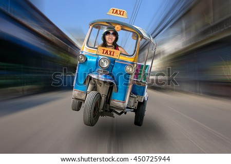 Traditional tricycle taxi rushing on the streets of Bangkok. Crazy ride of Tuk Tuk in the Thai road. Cheerful holiday in Thailand. - stock photo