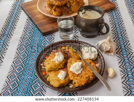 Traditional Ukrainian homemade potato pancakes potato, carrot and pumpkin with sour cream and glass of vodka - stock photo