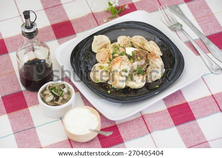 traditional ukrainian small pockets of dough filled with minced meat - pelmeni, served with sour cream, pickled mushrooms and soy sauce