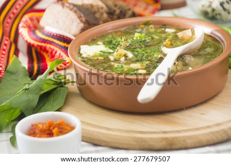 Traditional ukrainian sorrel, meat and eggs autumn soup green borsch in ceramic basin  served with rye bread and chili pepper, garlic and carrot hot sauce