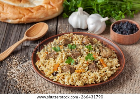 Traditional uzbek meal called pilaf. Rice with meat, carrot and onion in vintage plate on wooden background - stock photo