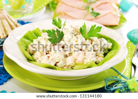 traditional vegetables salad with ham and mayonnaise on white plate