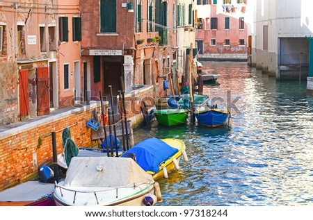 Traditional venetian canal with boats, Italy - stock photo