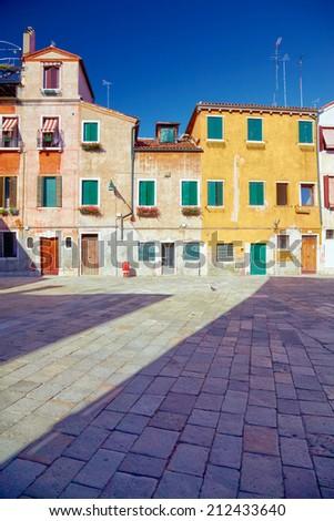 Traditional Venetian houses and yard under blue sky, Venice, Italy - stock photo
