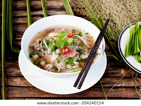 Traditional Vietnamese beef soup pho on a wooden background - stock photo