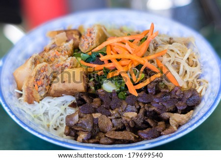 Traditional Vietnamese bun vermicelli salad with charbroiled meat, shredded pork, deep fried spring rolls and pickled carrots served with onions, bean sprouts and fish sauce.  - stock photo