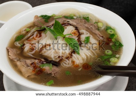Traditional Vietnamese soup with beef and rice noodles, top view.