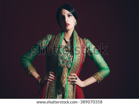 Traditional vintage Bollywood fashion girl against dark red background. - stock photo