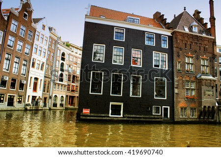 Traditional water streets and water canals next to in the city houses in city of Amsterdam, Holland.