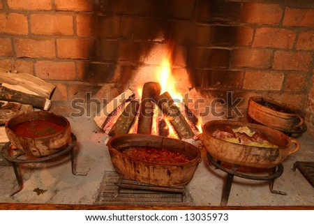 Traditional way of cooking by open fire in clay pot on tripod - stock photo