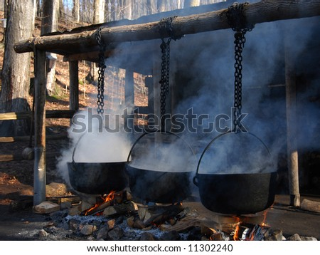 Traditional way of making maple syrup by boiling the sap in a cauldron - stock photo