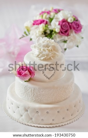 Traditional wedding cake and bridal bouquet - stock photo