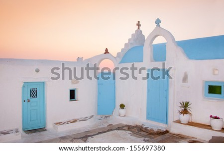 Traditional white-blue Greek family church near the sea at sunset - stock photo