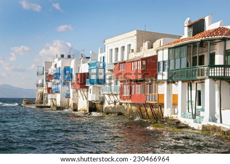 Traditional whitewashed buildings built on the edge of the coastline with the Aegean sea below, Mykonos town, Cyclades, Greece. - stock photo