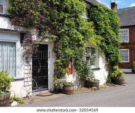 Traditional whitewashed English Village Cottage with climbing plants on the Wall and Postbox