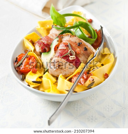 Traditional wide Italian pappardelle egg noodles with bacon, tomato, fresh herbs and spicy seasoning served in a bowl high angle view - stock photo