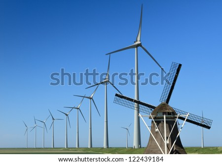 Traditional windmill 'De Goliath' and modern wind turbines in the Eemshaven, the Netherlands. - stock photo