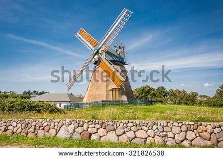 Traditional windmill in beautiful scenery with blue sky and clouds on a sunny day in summer - stock photo