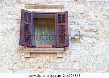 Traditional window with wood shutters wide open on stone facade of Mediterranean house, Pula, Croatia - stock photo