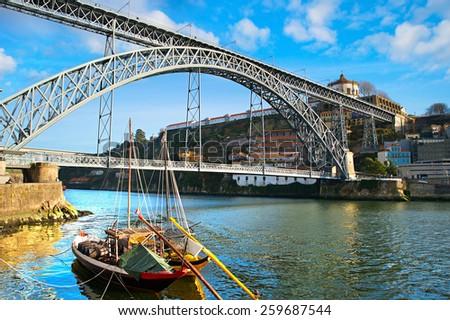 Traditional wine boats and Dom Luis I bridge in Porto, Portugal - stock photo