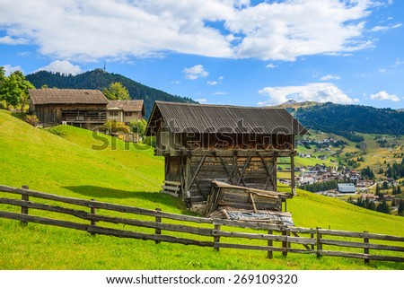 Traditional wooden barn on green meadow in alpine village on sunny day, Dolomites Mountains, Italy - stock photo