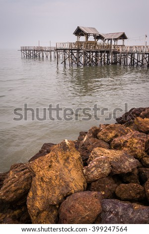 Traditional wooden boardwalk and shelter in Malaysia. Used for conventional fishing boats and fishermen. - stock photo